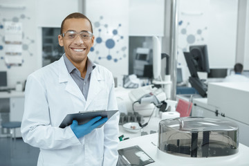 Young scientist watching laboratory machine during an experiment