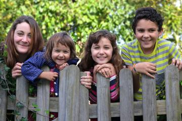 Portrait Vier lachende Geschwister schauen über den Gartenzaun