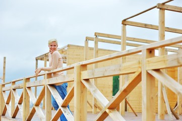 Outdoors portrait of beautiful emotional young blonde woman standing on the unfinished wooden deck and looking to side, smiling happily.