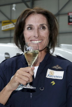 British aviator Tracey Curtis-Taylor holds a glass of champagne as she celebrates her arrival at Sydney's International Airport in an open cockpit biplane