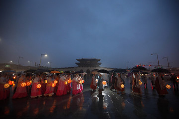 Monks and Buddhists holding lanterns walk during a lighting ceremony in central Seoul