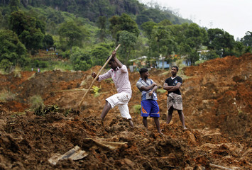 Man searches at the site of a landslide near Haldummulla
