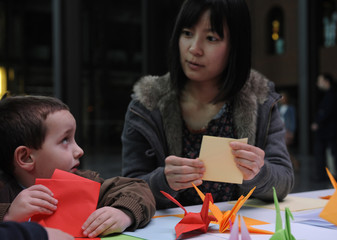 A helper folds a paper crane during a origami session called Senbazuru in favour of disaster victims in Japan in the Ahondiga cultural centre in Bilbao.
