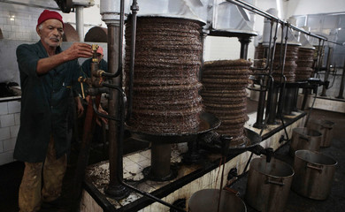 A worker keeps watch as olive paste is pressed to extract oil at a traditional olive oil processing factory in Tebourba