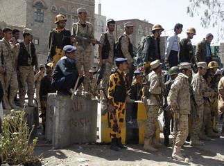Police and army troopers block a street leading to the cabinet's headquarters, during a demonstration demanding for the government to be dismissed, in Sanaa