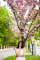 Girl with sakura tree flowers. Spring concept