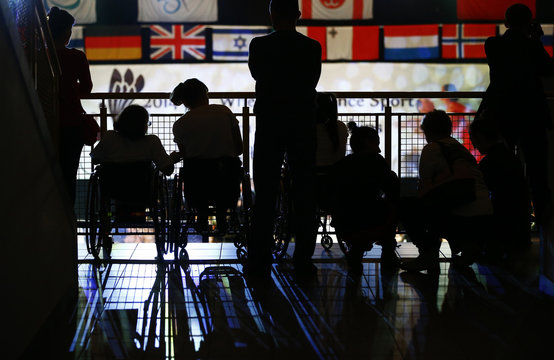 People are silhouetted as they watch the competition during IPC Wheelchair Dance Sport European Championships in Lomianki near Warsaw