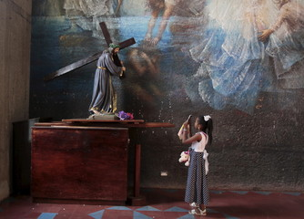 A girl uses her mobile phone to take pictures of a statue of Jesus at the Metropolitan Cathedral in Managua