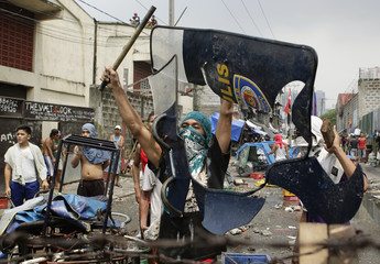 An illegal settler holds up a broken shield that he grabbed from the riot police during a demolition near Manila's Makati financial district