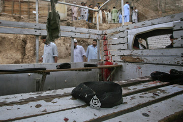 The hat of a policeman lies in the back of a vehicle which was hit by a bomb in Peshawar