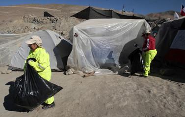 Workers pick up trash around Camp Esperanza in Copiapo
