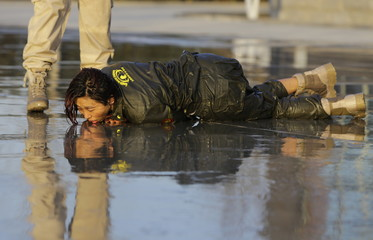 Female trainee lies on the ground after being drenched with water during Tianjiao Special Guard/Security Consultant training on the outskirts of Beijing