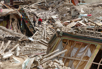 Ethnic Tibetans search for belongings amid the debris of collapsed houses in the earthquake-hit town of Gyegu in Yushu County