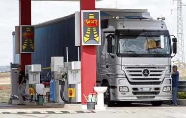 An attendant prepares to refuel a truck at a petrol station in Viterbo