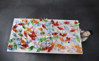 A child looks up from a table covered in paper cranes during a origami session called Senbazuru in favour of disaster victims in Japan in the Ahondiga cultural centre in Bilbao.