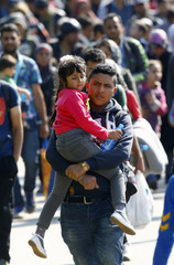 A migrant carries a girl as he walks towards the Austrian border from Hegyeshalom