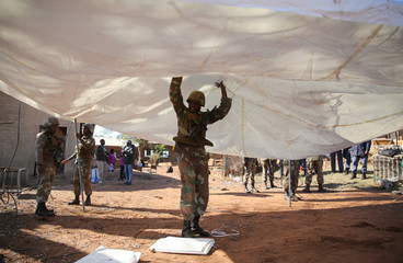 SANDF member helps set up a tent to be used as a poling station in Vuwani