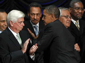 U.S. President Barack Obama is hugged by Rep. Barney Frank (D-MA) and applauded by Senator Christopher Dodd (D-CT) in Washington
