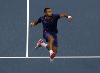 Tsonga of France jumps as he celebrates winning his first round match against Istomin of Uzbekistan at the China Open tennis tournament in Beijing
