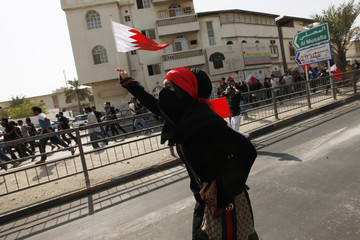 An anti-government protester runs towards riot police with a Bahraini flag in her hand during a demonstration after a funeral procession at Daih village