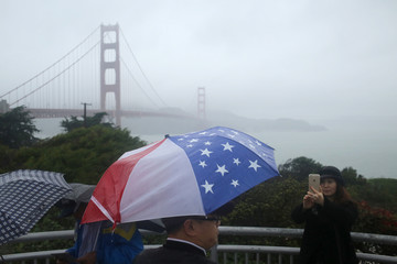 Tourists snap photographs at an overlook near the Golden Gate Bridge in San Francisco
