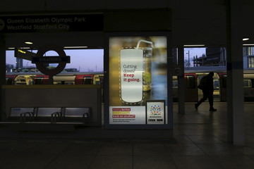 A man walks past a poster for the Drinkaware app at Stratford underground station in London
