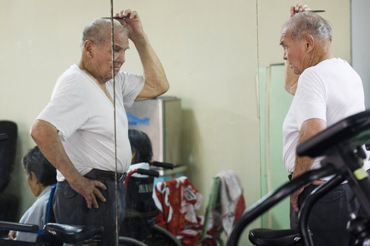 An elderly man combs his hair at the physical therapy room in the Canevaro old people's home in Lima