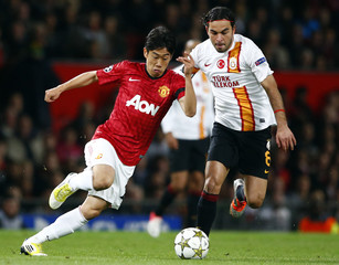 Manchester United's Kagawa challenges Galatasaray's Inan during their Champions League Group H soccer match in Manchester
