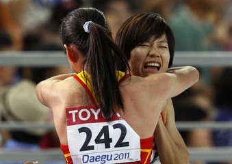 Wei of China embraces a teammate after the team was disqualified from their women's 4x100 metres heat in Daegu