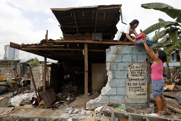 A family salvages belongings from their half-demolished house at a slum area in Quezon City
