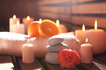 Beautiful spa setting with candles on wooden background