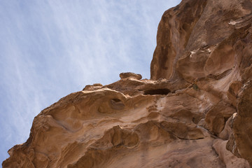 The steep sandstone walls of a natural mountain fault that leads to the Treasury, Al Khazneh, in Petra, Jordan. The caravan passage is called Al-Siq. Walls are viewed from below with blue sky above.