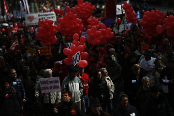 Demonstrators take part in a protest against the local government's plans to cut spending on public healthcare in Madrid