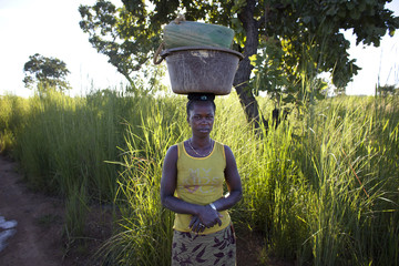 A small-scale gold miner carrying her tools on her head poses for a picture before heading home after working in Kalana