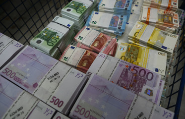 Wads of euro banknotes are stacked in a pile at the Money Service Austria company's headquarters in Vienna