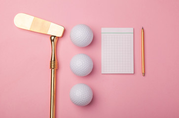 blank notepad, pencil, luxury golden golf club with golf balls isolated on pink background