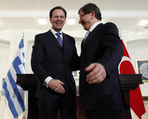 Turkish Foreign Minister Davutoglu and Greek Deputy Foreign Minister Droutsas gesture in Ankara