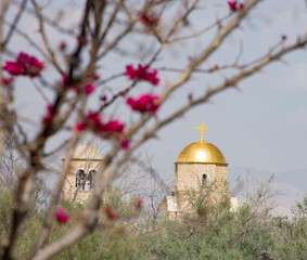 St. John the Baptist Orthodox Church at Bethany near the Jordan River. The sunlit gold dome is topped with a cross. A blooming bougenvilla is in the foreground.