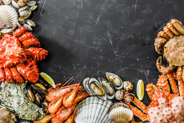Seafood cuisine plate as an ocean gourmet dinner background. Crab, seashells, oysters and other seafood delicacies.