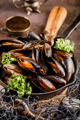 Frying pan with cooked mussels. Seafood dinner background.