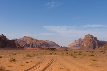 Four wheeling road through orange or rust colored sand with rugged mountains in the distance with deep blue sky above. Photographed in Wadi Rum Desert, Jordan under natural light.