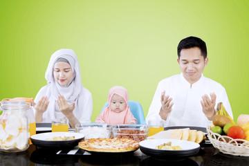 Muslim family praying before eating
