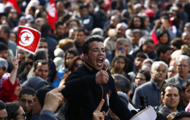 Tunisians chant slogans and hold flags during a ceremony marking 40 days since the assassination of leftist politician Chokri Belaid, in Tunis