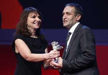 Jury member Bier presents actor Mujic with his Silver Bear award for Best Actor for the movie An Episode in the Life of an Iron Picker during the awards ceremony at the 63rd Berlinale International Film Festival in Berlin