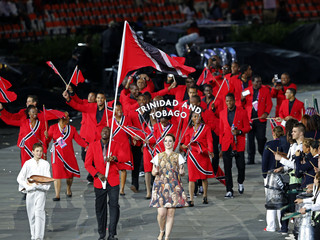 Trinidad and Tobago's flag bearer Marc Burns holds the national flag as he leads the contingent in the athletes parade during the opening ceremony of the London 2012 Olympic Games
