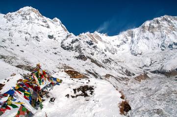 Widok na ośnieżoną Annapurnę i flagi modlitewne z bazy pod szczytem.