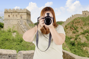 Woman with digital camera on g