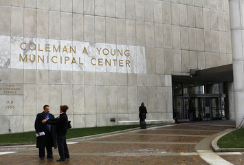 People stand outside the Coleman A. Young Municipal Center in Detroit