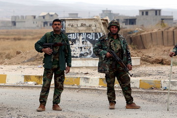 Kurdish peshmerga forces stand in the street after Yazidi people loot houses in the town of Sinjar