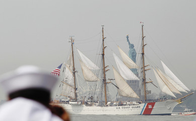 A member of the U.S. Navy takes pictures of the United States Coast Guard cutter Eagle as it passes the Statue of Liberty in New York Harbor